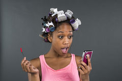 A girl with curlers in her hair looking at phone Royalty Free Stock Photo