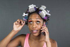 A girl with curlers in her hair talking on phone Royalty Free Stock Images