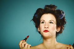 Girl in curlers styling hair applying make up Royalty Free Stock Photography