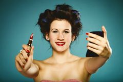 Girl in curlers styling hair applying make up Stock Photo