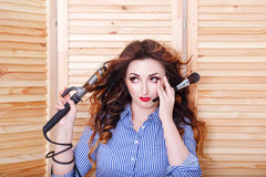 Girl with curling irons and brush for makeup Royalty Free Stock Photos