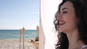 Girl with curls, gesture hello and smile, drinks cocktail сoconut, exoticism, summer season, on background sea ocean stock video