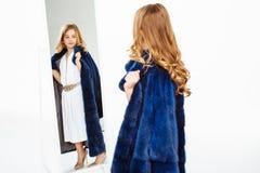 Girl with curls posing in fake fur coat admiring image. Stock Images
