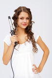 Girl with curly hair. Biting hair dryer Stock Images