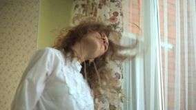 Girl curly hair, actively twists her head, playful, listens to music in the headphones by the window, the phone in her. Hands, dances, singing. portrait fhd stock video footage
