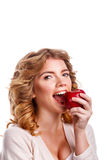 Girl with curly hair biting a red apple. Young beautiful girl with curly hair biting red ripe apple. Beautiful smile. White teeth. The concept of healthy teeth stock photo