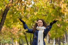 A girl with curly hair throws autumn leaves Royalty Free Stock Image