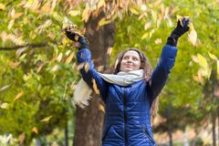 A girl with curly hair throws autumn leaves Stock Images