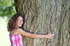 Girl with curly hair embracing a tree Royalty Free Stock Photos