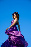 Girl with curly hair flying in the purple dress. Portrait of a beautiful girl with curly hair flying in the purple dress on the background of sky Stock Image