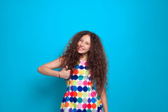 Girl with curly hair gesturing ok. Young pretty girl with messed up curly hair gesturing thumb up with blue screen on background Royalty Free Stock Photos