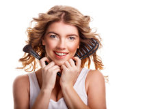 Girl with curly hair holding makeup brush and comb. Royalty Free Stock Photo