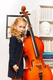 Girl with curly hair holds string to play cello Stock Image