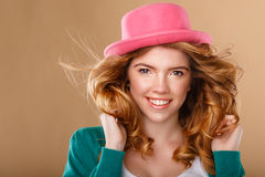 Girl with curly hair in a pink hat. Royalty Free Stock Photo