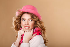 Girl with curly hair in pink hat and scarf. Stock Image