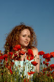 Girl with curly hair in poppies royalty free stock image