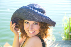Girl with curly hair in a purple hat. Portrait of a beautiful girl with curly hair in a purple hat on a background of the river Royalty Free Stock Image