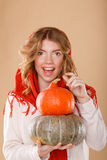 Girl with curly hair in a scarf. Girl holding pumpkin. Stock Photo