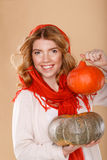 Girl with curly hair in a scarf. Girl holding pumpkin. Stock Photography