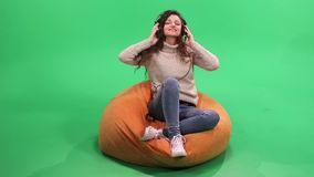 Girl with curly hair sitting on bean bag and listening music stock video