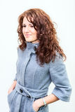 Girl with curly hair standing on a white background in coat Royalty Free Stock Image