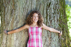 Girl with curly hair stands in front of a tree Royalty Free Stock Photo