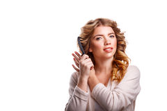 Girl with curly hair straightens hair comb. Stock Photos