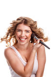 Girl with curly hair straightens makeup brush. Royalty Free Stock Images