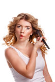 Girl with curly hair straightens makeup brush. Stock Photo