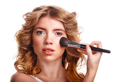 Girl with curly hair straightens makeup brush. Stock Photos