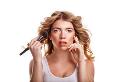 Girl with curly hair straightens makeup brush. Stock Images