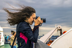 Girl with curly hair is taking a picture. Girl with curly and ruffled hair is taking a picture on the deck Stock Image