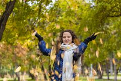 A girl with curly hair throws autumn leaves Royalty Free Stock Photo