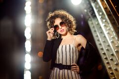 A girl with curly hair wearing sunglasses and white earrings
