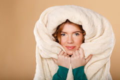 Girl with curly hair wrapped in a warm blanket. Stock Photos