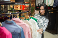 Girl customer choosing shirt in clothing store Stock Images