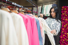 Girl customer choosing shirt in clothing store Stock Image