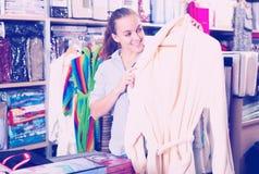 Girl customer deciding on the choice of bathrobe Royalty Free Stock Photo