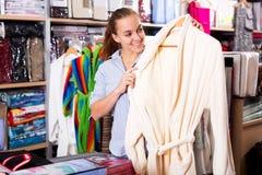 Girl customer deciding on the choice of bathrobe Royalty Free Stock Image