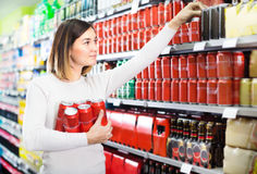 Girl customer looking for beer cans. In a supermarket Royalty Free Stock Photo