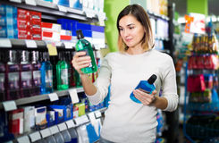 Girl customer looking for effective mouthwash in supermarket royalty free stock image