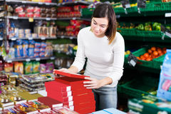 Girl customer looking for tasty sweets in supermarket Royalty Free Stock Photo