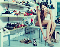 Girl customer trying on chosen shoes in footwear department Stock Images