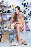 Girl customer trying on chosen shoes in footwear department Stock Image