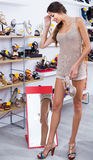 Girl customer trying on chosen shoes in footwear department Royalty Free Stock Photography
