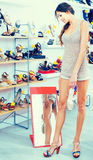 Girl customer trying on chosen shoes in footwear department Royalty Free Stock Photo
