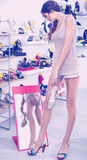 Girl customer trying on chosen shoes in footwear department Royalty Free Stock Images