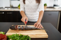 Girl cut fish to cook tasty dish Stock Photography
