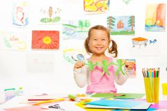 Girl and cut paper men. Happy smiling Asian girl holding paper green mans cut out Stock Photography