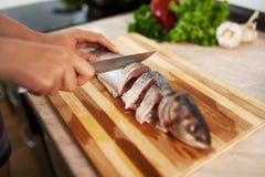 Girl cut slice of  fish Stock Photo